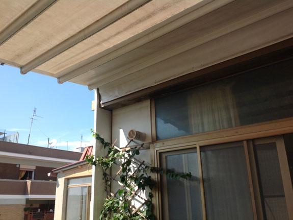 Fotografia di una Pergotenda modello Evolution con telo in PVC bianco. Struttura in alluminio verniciato bianco (9010). Tenda TX frontale ad arganello. Montaggio sul terrazzo di un attico ad Ostia.