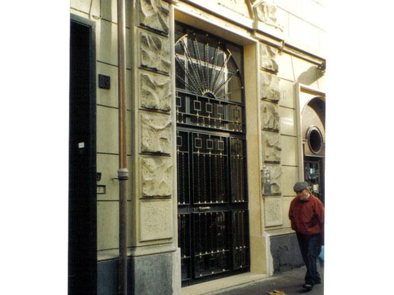Fotografia diun Portone condominiale in ferro prezincato e verniciato grigio micaceo completo di profili esterni a torciglione con inserti in ottone e quadrelli da 14 mm. Montaggio a Roma Appia nuova.