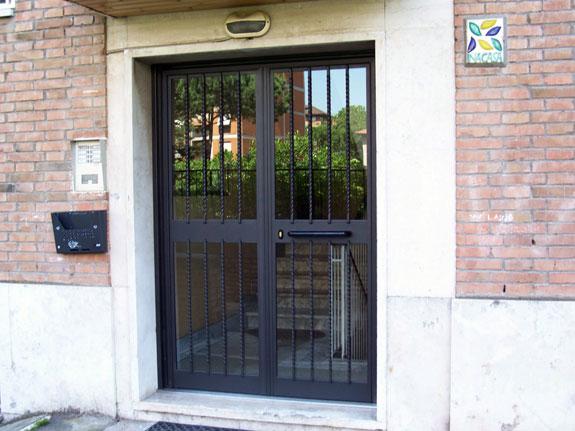 Fotografia di un Portone condominiale in ferro prezincato e verniciato nero micaceo completo di torciglioni esterni. Montaggio a Roma, quartiere Casilino.