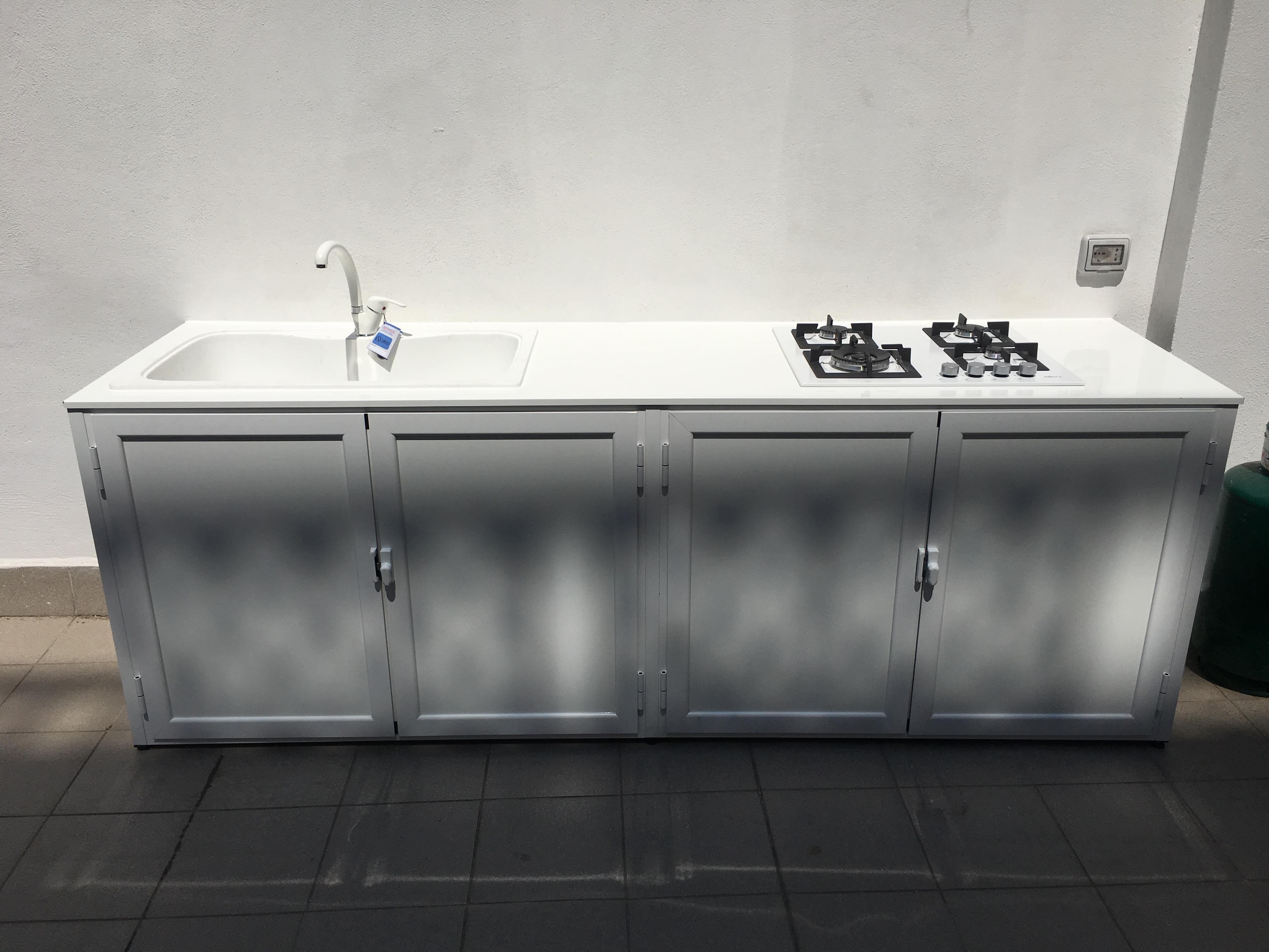 Fotografia di un armadio bianco 9010 pannellato liscio con top in lamiera, lavandino e piano cottura a incasso.