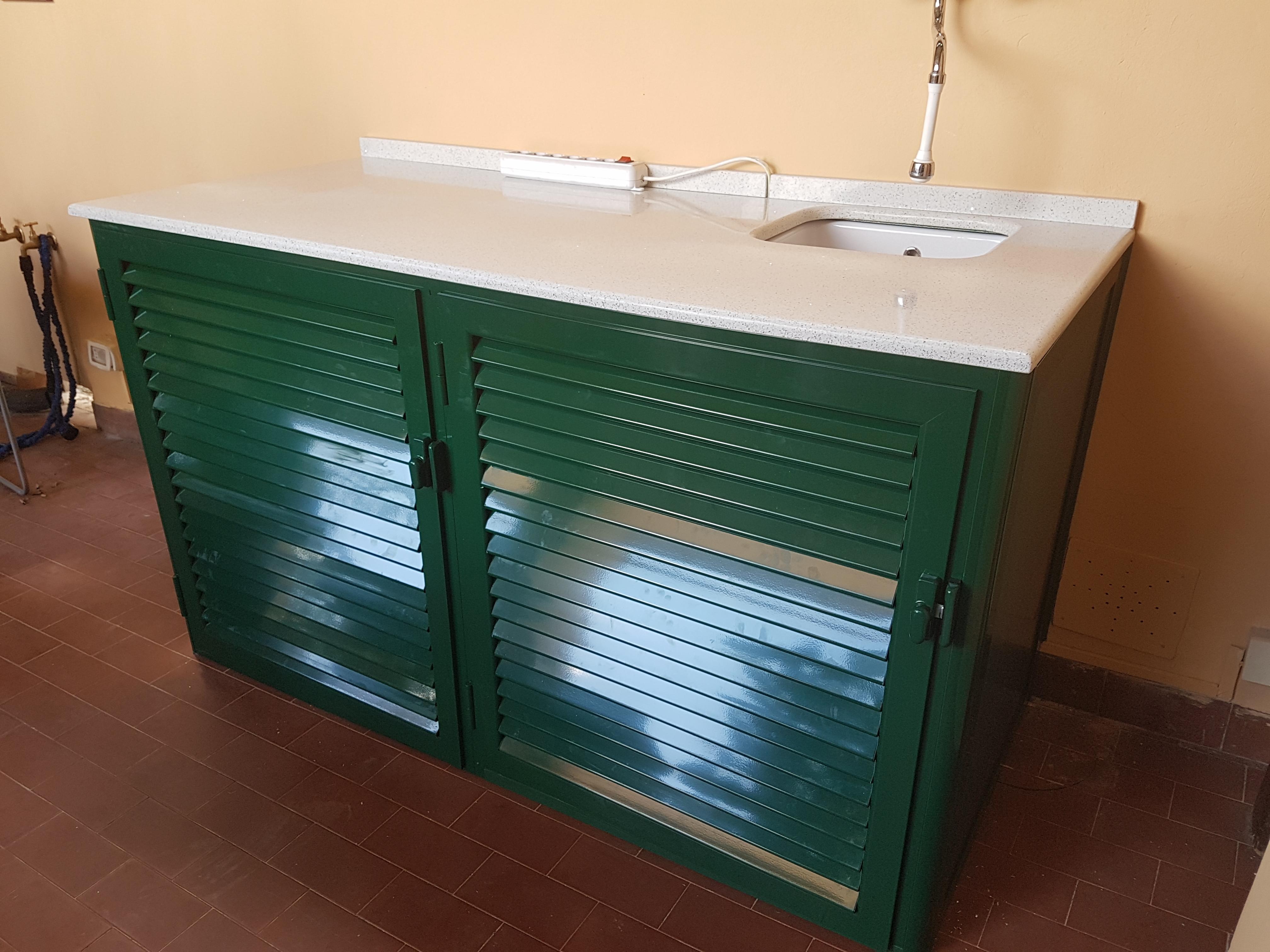 Fotografia di un armadio verde 6005 a doghe chiuse coprilavatrice con top in quarzo e lavandino sotto top (chiuso).