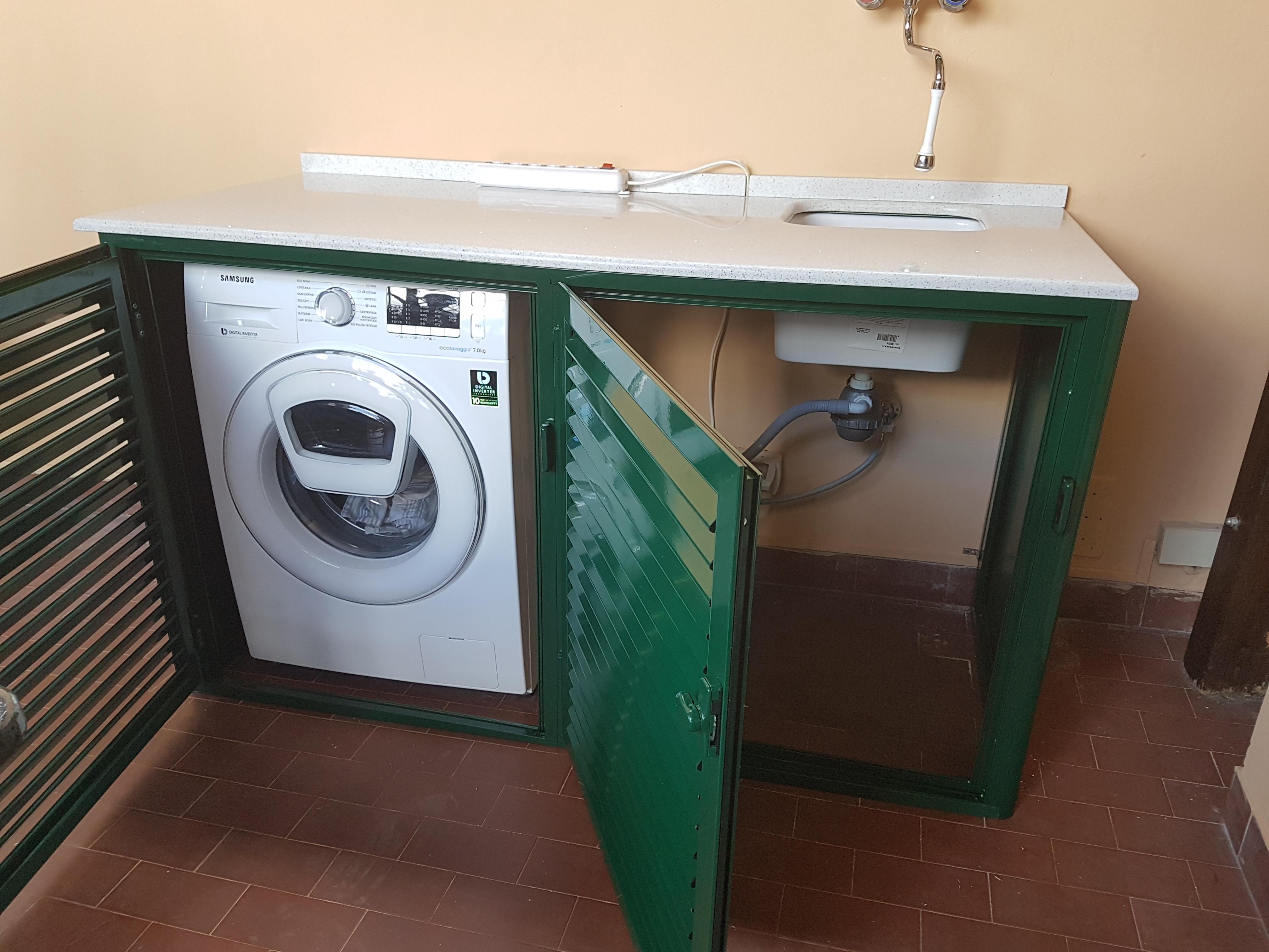 Fotografia di un armadio verde 6005 a doghe chiuse coprilavatrice con top in quarzo e lavandino sotto top (aperto).