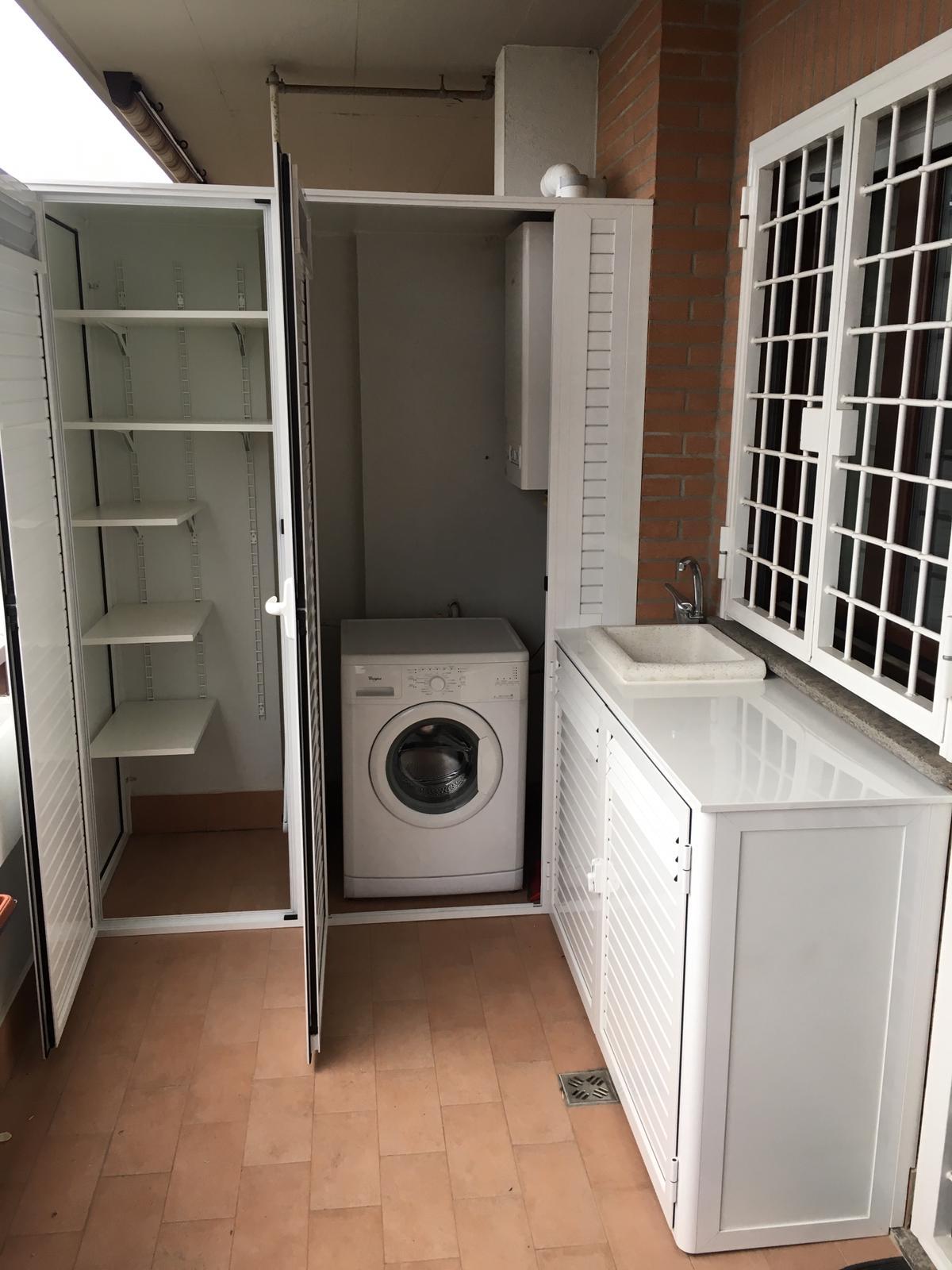 Fotografia di un armadio in alluminio bianco Ral 9010 a doghe chiuse e in parte aperte coprilavatrice e caldaia, parte bassa con top in lamiera e lavandino a incasso in marmo (aperto).