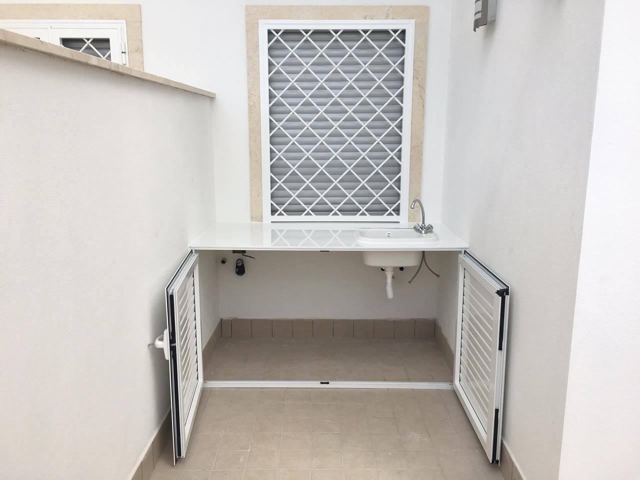 Armadio basso con piccolo lavandino a destra, sotto finestra con grata