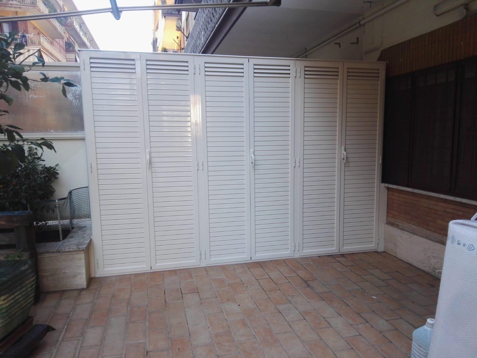 Fotografia di un armadio in alluminio avorio Ral 1013 a doghe chiuse e in parte aperte a 6 ante a uso ripostiglio (chiuso).