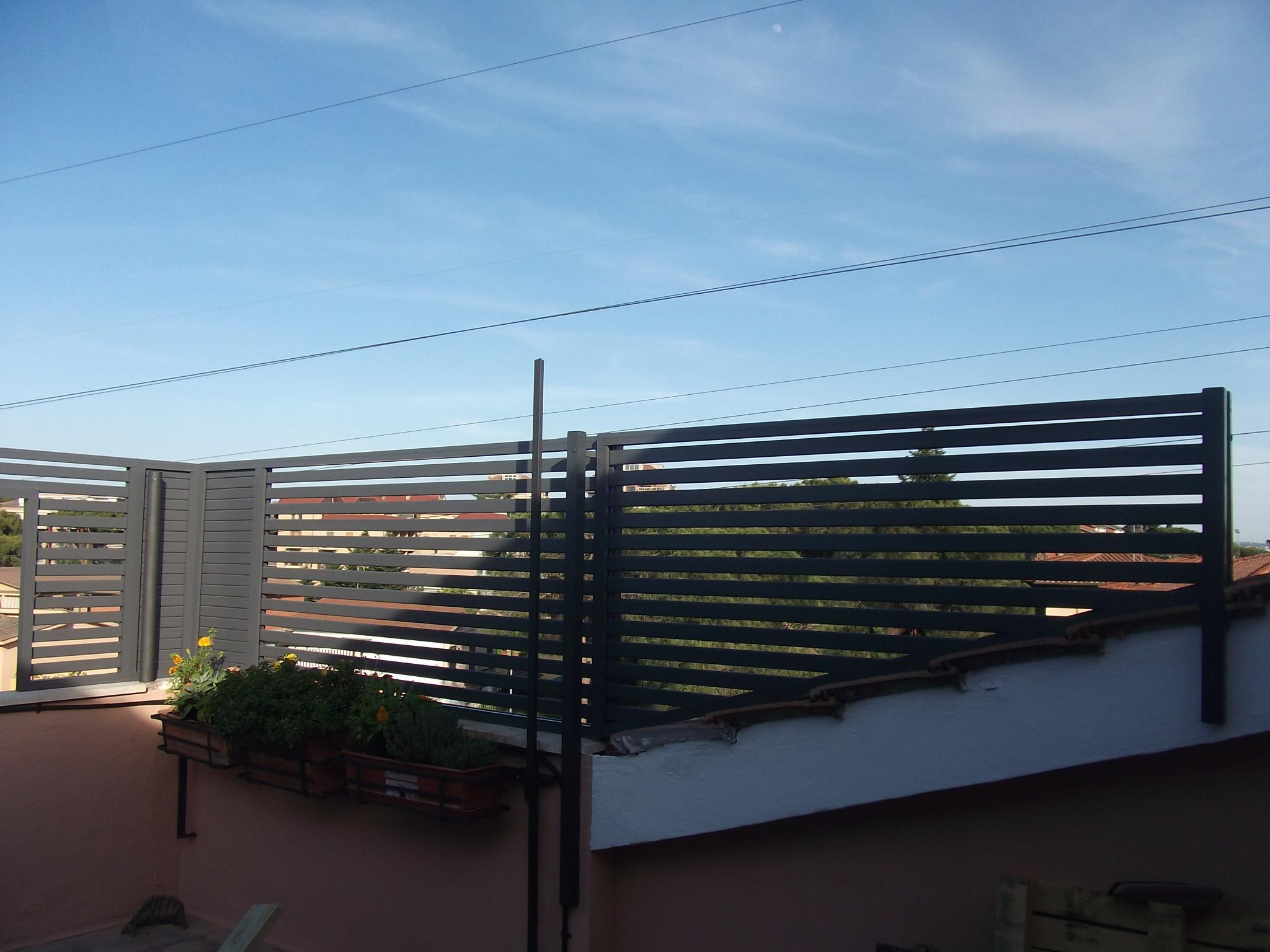 Fotografia di un frangisole in alluminio grigio Raffaello con profili orizzontali 50x10 mm. Montaggio su attico a Roma, quartiere Statuario.