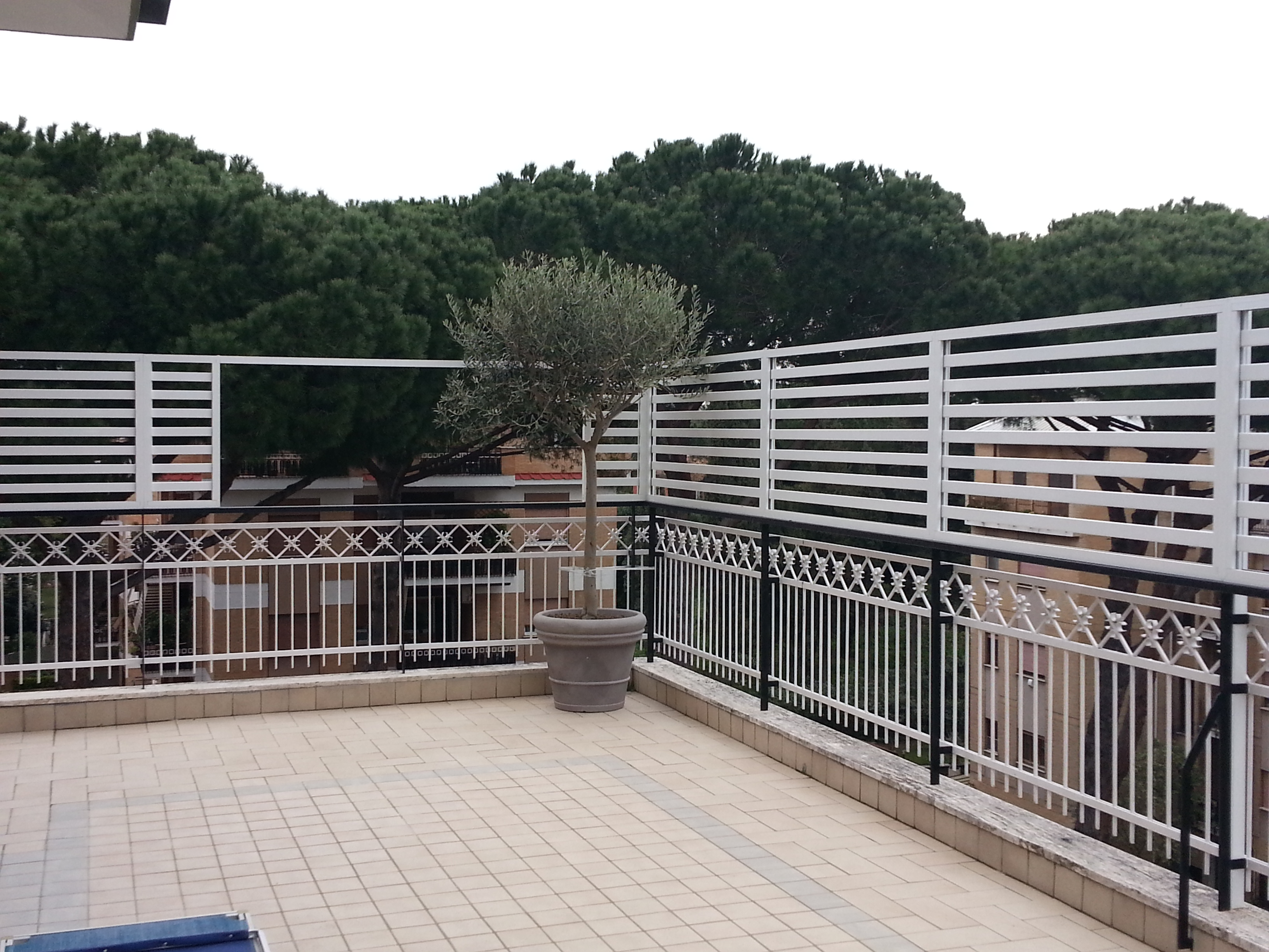 Fotografia di un Frangisole in alluminio verniciato bianco, spazio di cm. 4 tra le doghe. Montaggio sel terrazzo di un attico a Roma, quartiere Monteverde.