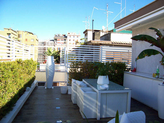 Fotografia di un frangisole in alluminio verniciato bianco, spazio di cm. 4 tra le doghe. Montaggio sul terrazzo di un attico a Roma, quartiere Appio Latino.