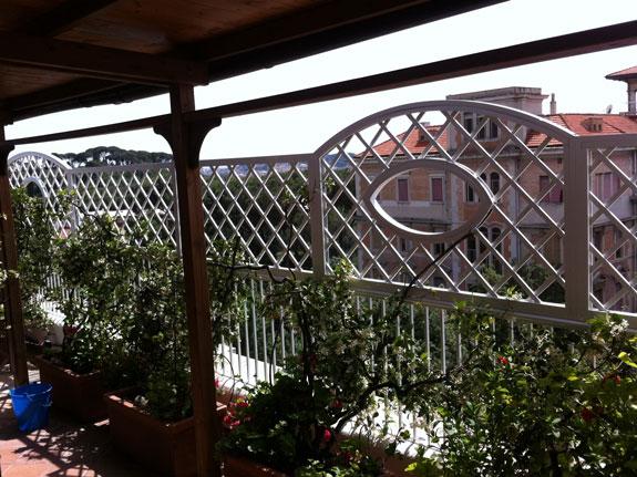 Fotografia di un Grigliato in alluminio bianco (9010) a maglia inclinata 11x11, telai alternati con archetto superiore e oblò, telai rettangolari. Montaggio a Roma Parioli.