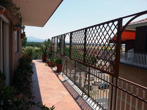 Fotografia di un Grigliato in alluminio effetto legno noce Francia (PKA16) a maglia inclinata 11x11, affacci ad archetto. Montaggio a Roma Tuscolana.