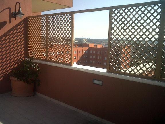 Fotografia di un grigliato ciliegio chiaro maglia 4,5x4,5 inclinata, affaccio dritto. Montaggio a Roma Eur.