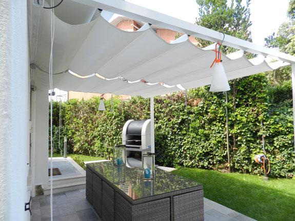 Fotografia di Tende modello Giardino in stoffa impermeabile bianca. Struttura in alluminio bianco (9010). Montaggio in un giardino a Fregene.
