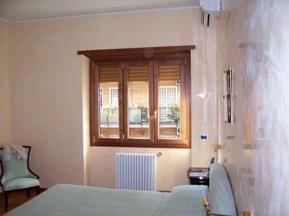 Fotografia di una Finestra in alluminio-legno All.Co. Wood ciliegio interno e bianco esterno. Apertura a battente.