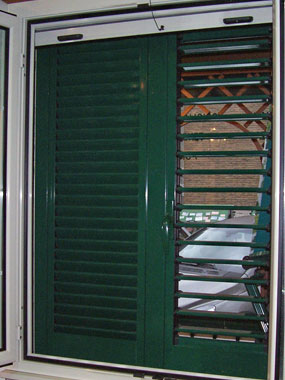 Fotografia di una persiana di colore verde scuro.