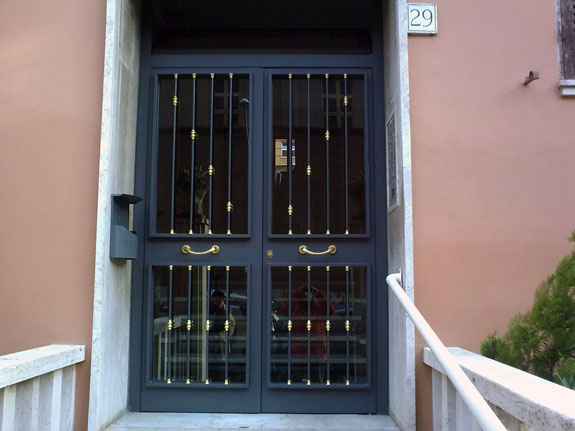 Fotografia di un Portone condominiale in ferro prezincato e verniciato grigio micaceo completo di profili esterni tondi con inserti in ottone. Montaggio a Roma, quartiere Appio Latino.