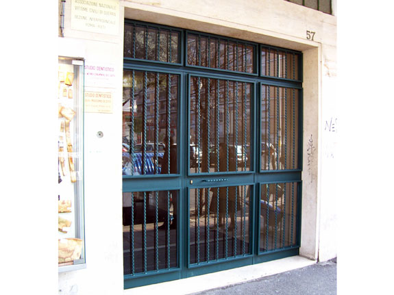 Fotografia di un Portone condominiale in ferro prezincato e verniciato verde completo di torciglioni esterni con basette in ottone. Montaggio a Roma, zona Marconi.