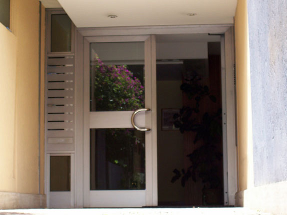Fotografia di un Portone condominiale in alluminio argento, completo di cassette postali. Montaggio a Roma EUR.