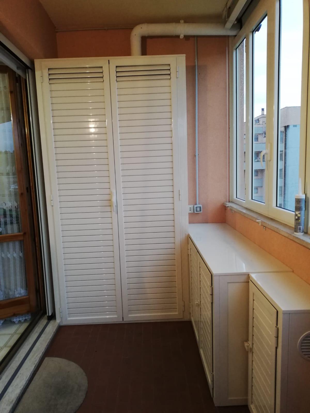 Fotografia di un armadio copricaldaia e ripostiglio in alluminio avorio a doghe chiuse e in parte aperte (chiuso).