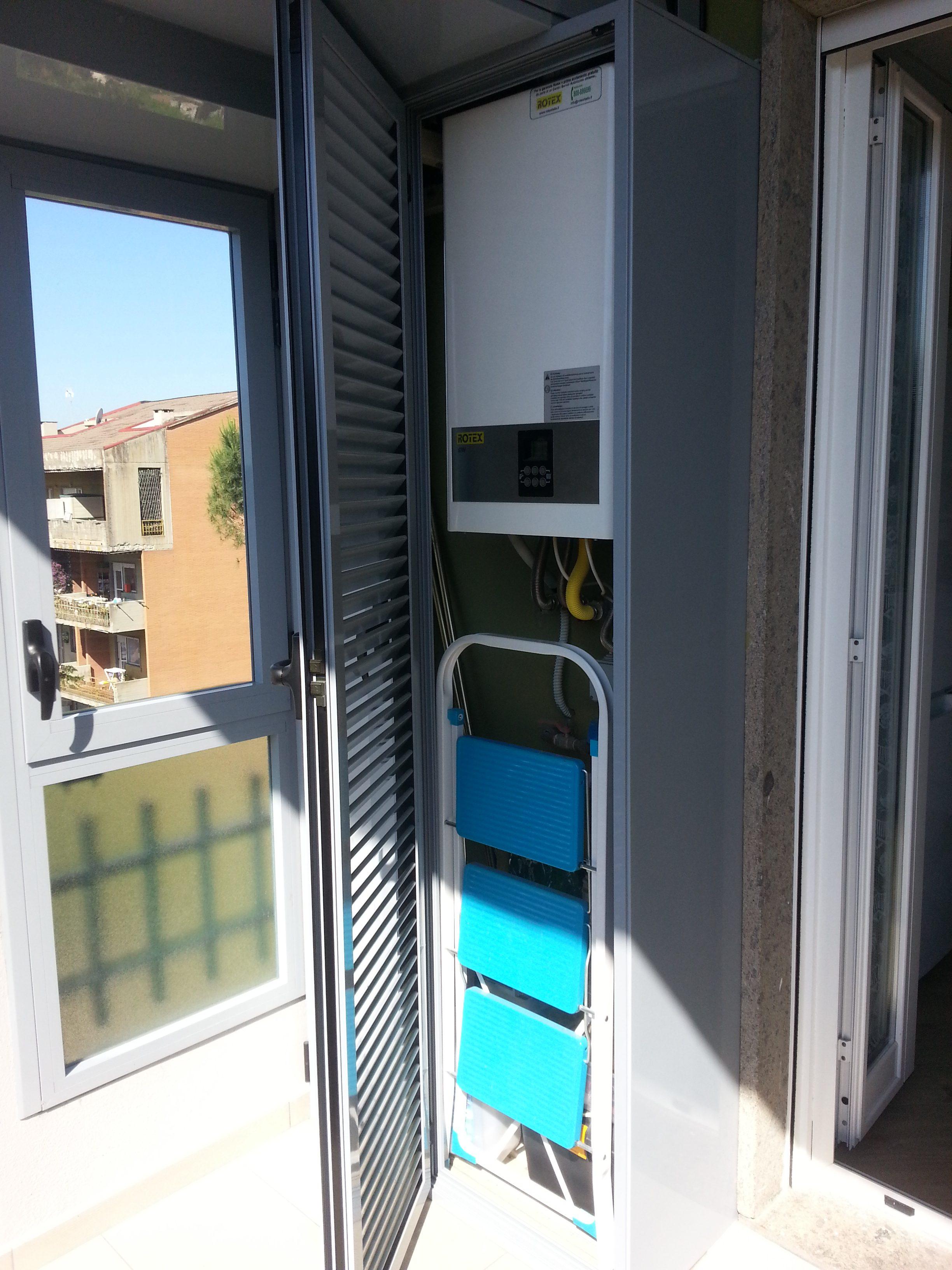 Fotografia di un armadio copricaldaia in alluminio grigio Ral 7001 a doghe inclinate aperte (aperto).