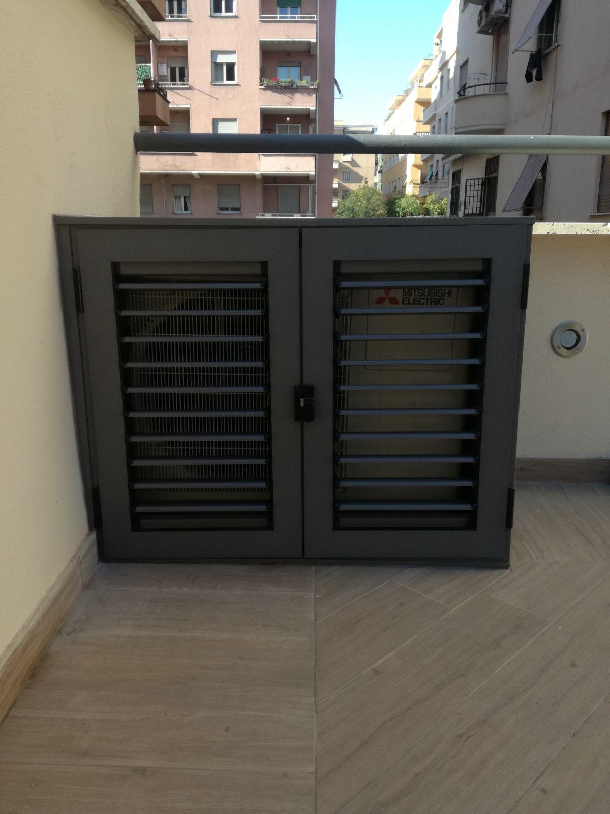 Fotografia di un armadio coprimotore in alluminio grigio micaceo a doghe orientabili (chiuso).
