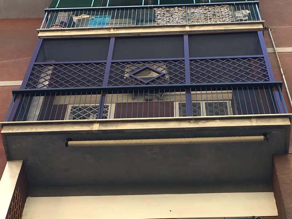 Fototgrafia di un grigliato con barriera di protezione zanzariera pet-screen montato su balcone a Roma
